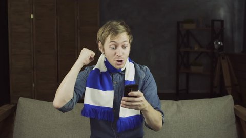 Young happy football fan winning a betting and watching a smart phone. Man celebrate win a bet with a gambling mobile app. Soccer bet