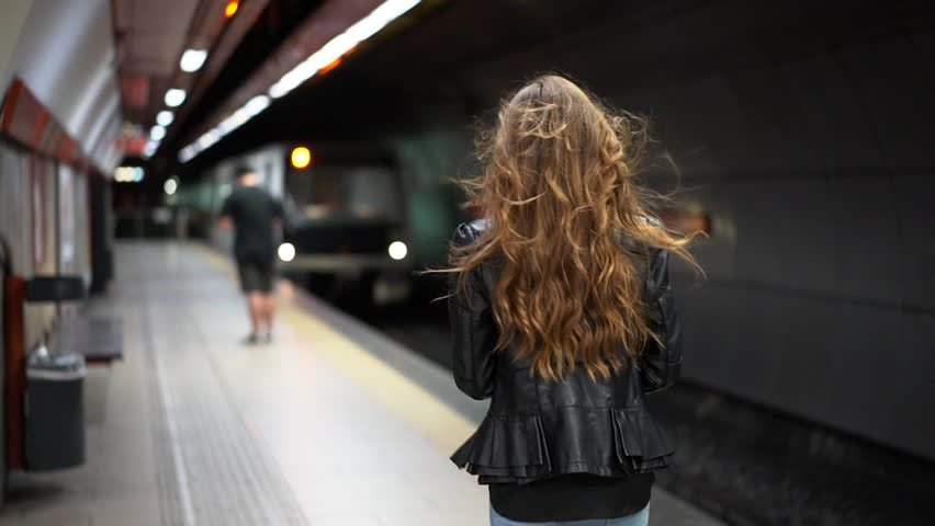 Attractive woman in an underground subway station checking her phone as a train arrives in slow motion | Shutterstock HD Video #1012737758