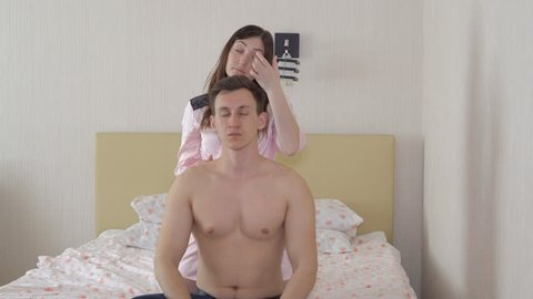 woman in a dressing gown doing a massage around the neck of a man in the bedroom.