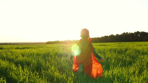 A happy child in a superhero costume in a red raincoat runs along a green lawn against the sunset, looking back.