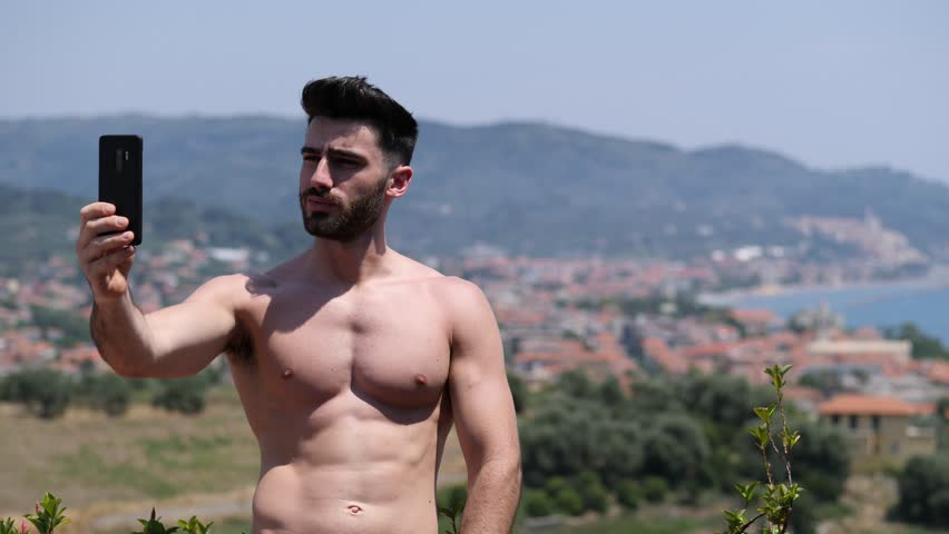 Young handsome man using smartphone, videocalling someone while standing shirtless on a balcony at the seaside over countryside landscape