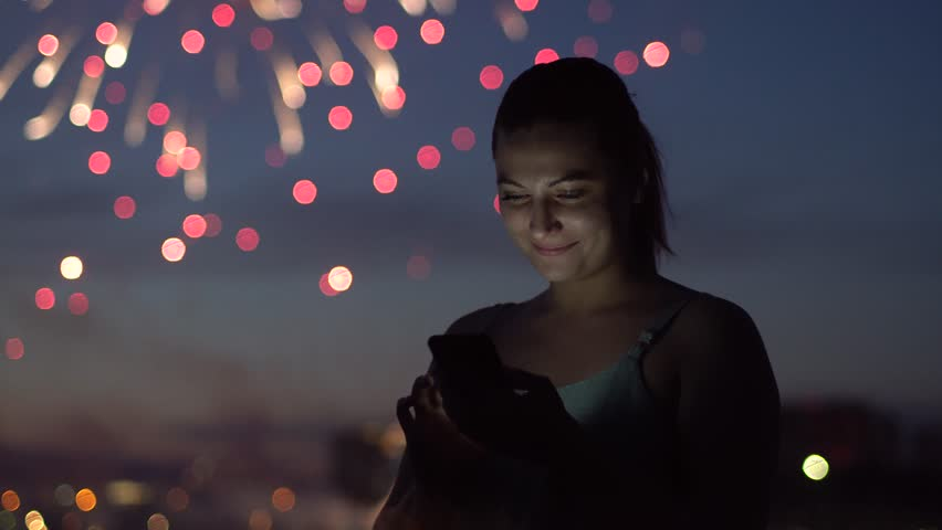 A girl uses a sartphone during a firework. 4K | Shutterstock HD Video #1012796708