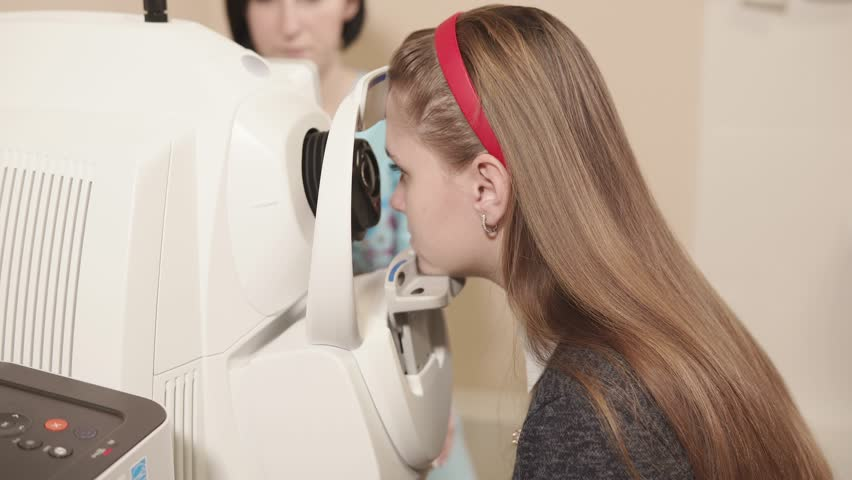 Side view shot of young girl having her eyes examed on eye tomography machine in hospital. Ophthalmologist's office.