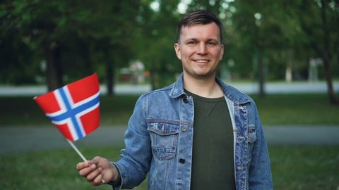 Slow motion portrait of Norwegian sports fan waving flag of Norway standing outdoors and smiling looking at camera. Supporting national team and countries concept.