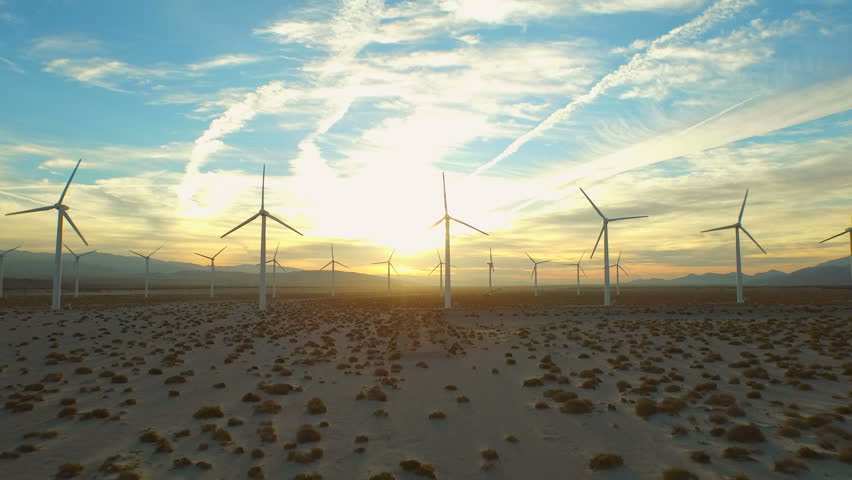 Wind Turbine Aerial v7 Flying low below large wind turbines at sunrise.