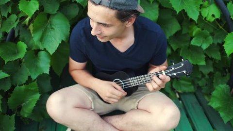 A guy plays the ukulele