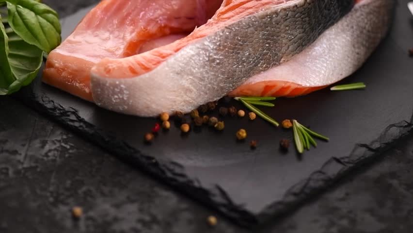 Salmon. Raw Trout Red Fish Steak with Herbs and Lemon and olive oil on slate. Cooking Salmon, sea food. Healthy eating concept. Slow motion 4K UHD video