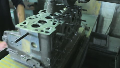 Worker grinding cylinder head and block on the machine  cylinder head and  block resurfacing  engine block repair process