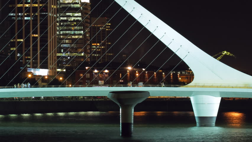 Puente de la Mujer footbridge and cityscape of Buenos Aires, Argentina, from Puerto Madero harbor at night. Photo time-lapse with cg-pan (1080p, DSLR).