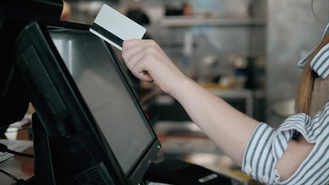 Side view of young bartender using modern cash register at bar counter