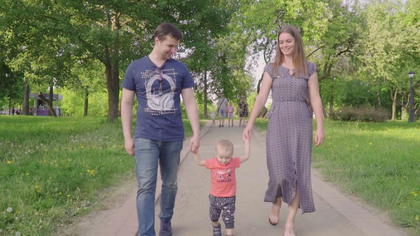 Beautiful family enjoying summer day in the park: little baby learning how to walk with mom and dad helping him to make his first steps | Shutterstock HD Video #1012912088