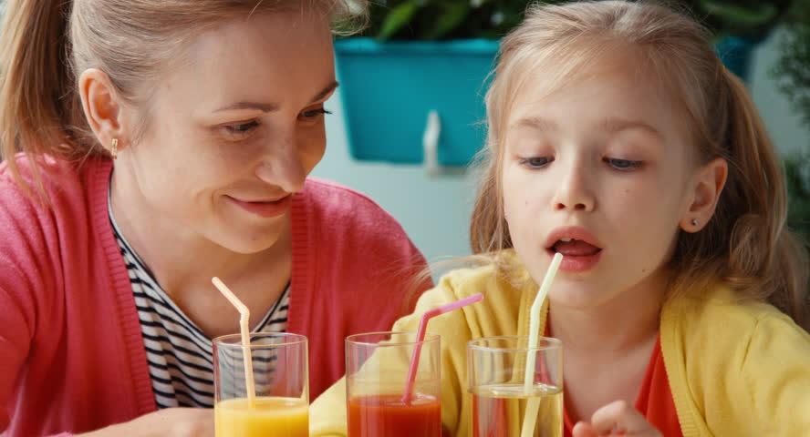 Mother and daughter drinking tomato and orange juice and looking at camera