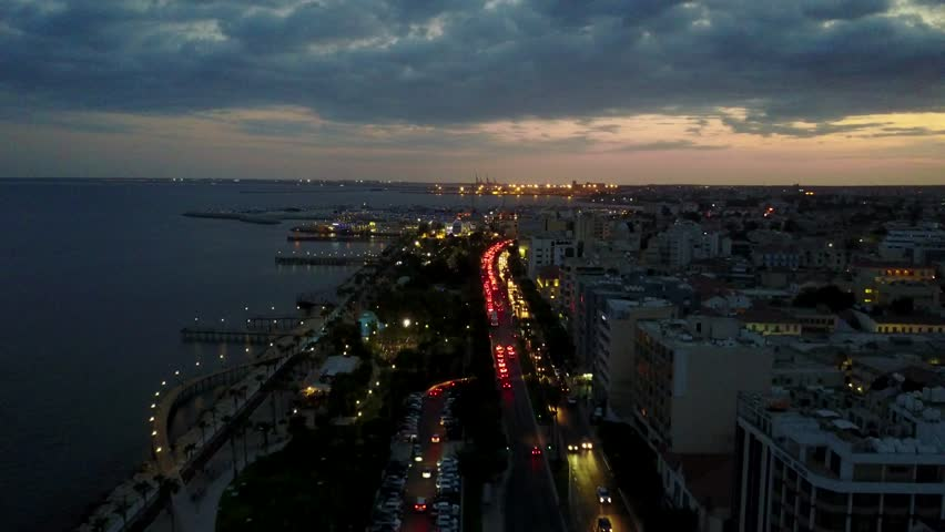 Aerial drone shot flying over a busy street at night with city lights of Limassol Cyprus