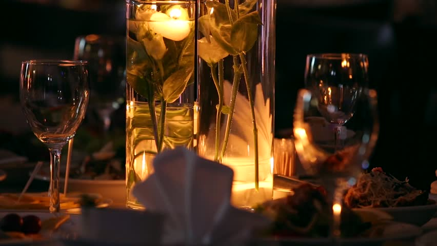 Wedding banquet hall interior details with decorated table setting at restaurant. Candles and white petals decoration with roses flowers in glass vases filled with water.
