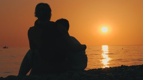 Back view of mom and son, silhouette, sitting hugging. Travel and enjoy the rays of the setting sun. Amazing sunset on the beach in summer. Happy family.