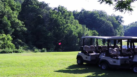 Wide establishing shot of an empty golf course with trees, golf carts, and flag blowing in the wind.  Peaceful view of a Golf Course on a sunny day.
