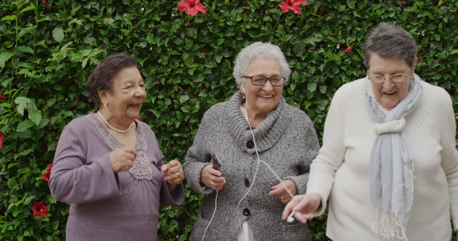 Portrait of diverse senior women dancing happy enjoying celebrating retirement listening to music together in outdoors garden