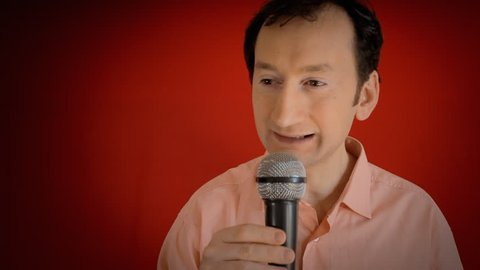 A funny ugly man speaking to an audience, waiting for the crowd to react, and then dropping the microphone (the famous mic drop gesture, a display of bold confidence). Close-up shot, red background.