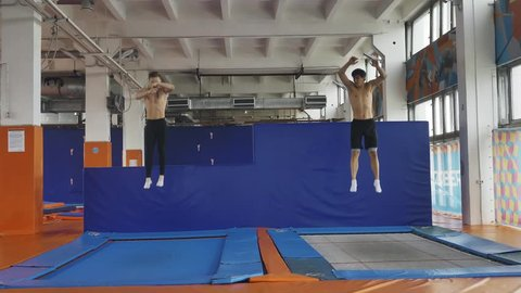 Two gymnasts jumping synchronously on trampolines, slow motion. Symmetry.