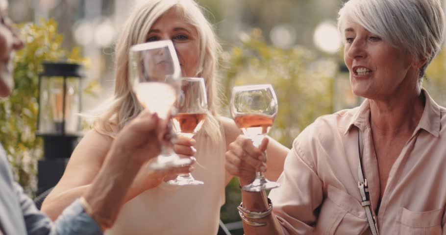 Happy mature women toasting and celebrating with wine while relaxing at luxurious restaurant patio
