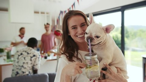 Pretty young woman holds her cute french bulldog puppy on her hands, and drinks homemade fresh summer drink out of the mason jar with straw, dog wants to taste some, she is happily smiling.
