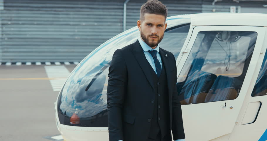 Portrait of young adult businessman executive standing near a private charter helicopter on a helipad. 4K UHD