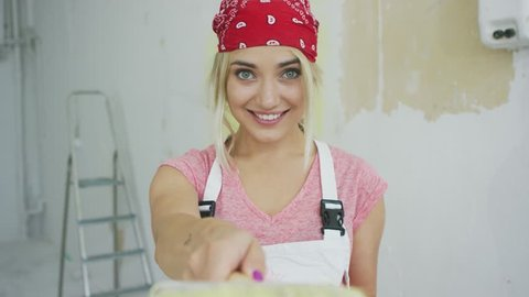 Crop view of gorgeous young blond woman in light clothes and red bandana standing at unpainted wall and smiling pointing with brush and looking at camera.