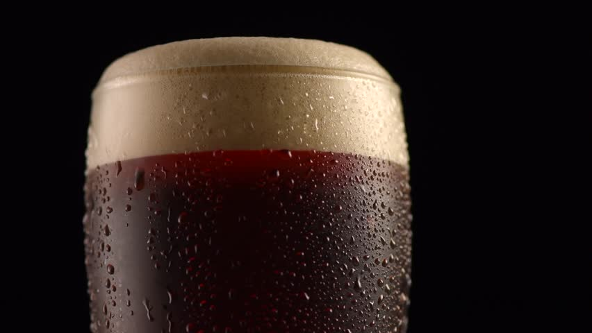 Dark Beer closeup. Pint of cold Craft beer isolated on matte black background, rotation 360 degrees. Glass of beer with water drops. 4K UHD video 3840x2160
