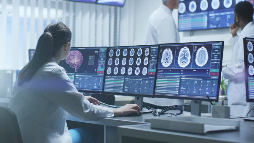 Team of Professional Scientists Work in the Brain Research Laboratory. Neurologists / Neuroscientists Surrounded by Monitors Showing CT, MRI Scans. Shot on RED EPIC-W 8K Helium Cinema Camera.