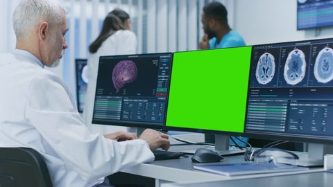 Scientist Working with Mock-up Green Screen and CT Brain Scan Images on a Personal Computer in Laboratory. Neuroglogists work in Neuroscience Medical Research Center. Shot on RED EPIC-W 8K Camera.