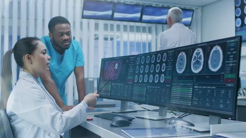 Medical Scientist and Surgeon Discussing CT Brain Scan Images on a Personal Computer in Laboratory. Neurologists / Neuroscientists in Neurological Research Center. Shot on RED EPIC-W 8K Helium Cinema