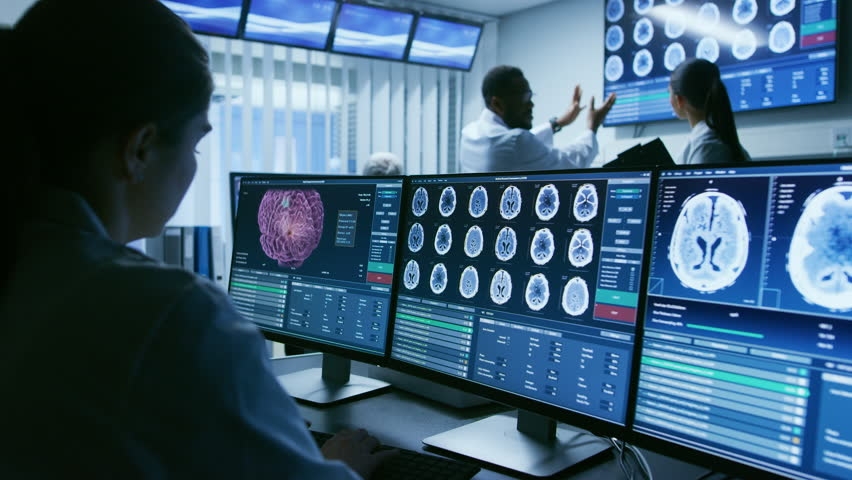 Over the Shoulder Shot of Female Medical Scientist Working with Brain Scan Images on a Personal Computer in Laboratory. Neurological Research Center. Shot on RED EPIC-W 8K Helium Cinema Camera.