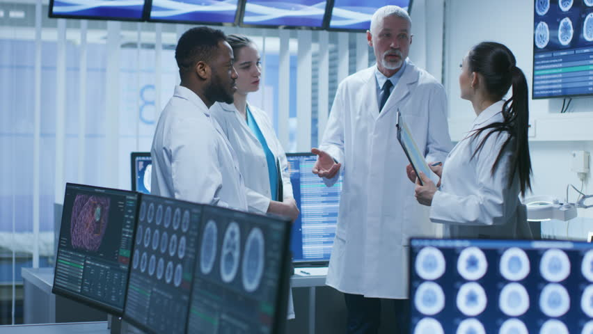 Meeting of the Team of Medical Scientists in the Brain Research Laboratory. Neurologists / Neuroscientists Having Heated Discussion Surrounded by Monitors Showing CT, MRI Scans. Shot on RED EPIC-W 8K.