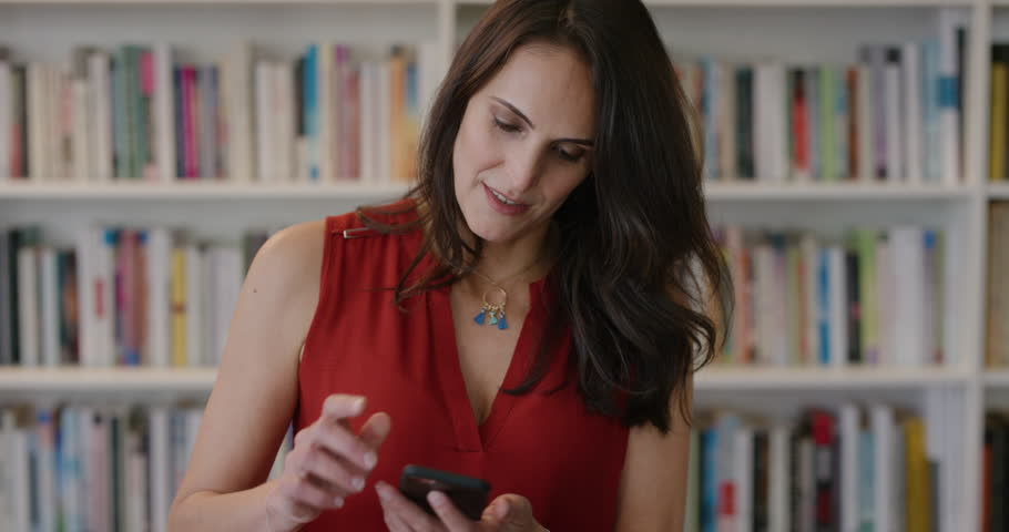 Portrait beautiful mature business woman using smartphone browsing online messages enjoying mobile communication stylish independent female in library bookstore real people series | Shutterstock HD Video #1013095358