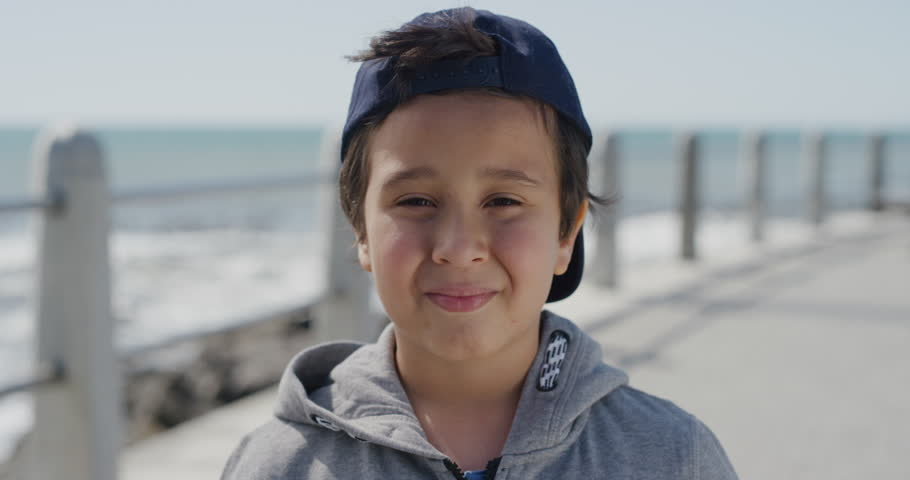 Portrait of young hispanic boy smiling cheerful looking at camera enjoying summer day on seaside park real people series | Shutterstock HD Video #1013096618