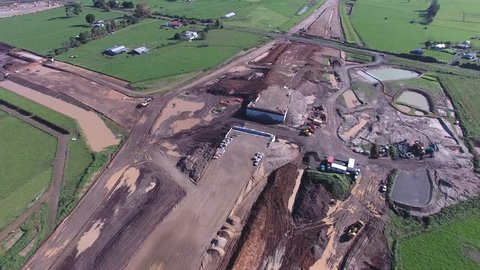 Aerial of highway interchange bridge under construction early stage with abutments and earth works through farmland