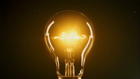 Light bulb on dark background with shine. Conceptual image. The word LIGHT can be read on the filament