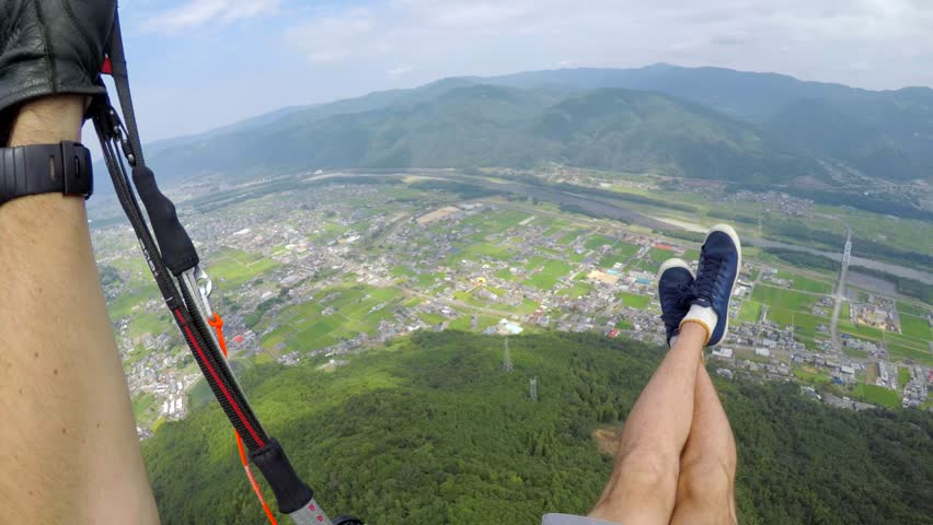 Solo paraglider helmet cam footage looking at the break handle and wing while flying over a Japanese town with a river in the background