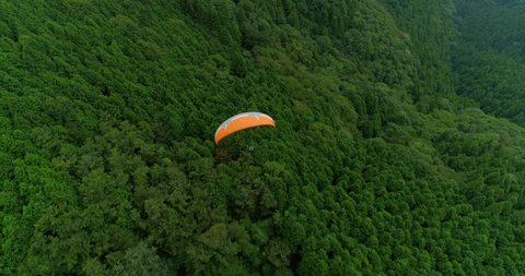 Aerial close follow shot of paraglider flying over the lush Japanese mountain ridges