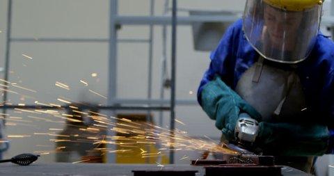 Young female welder using grinder in workshop 4k