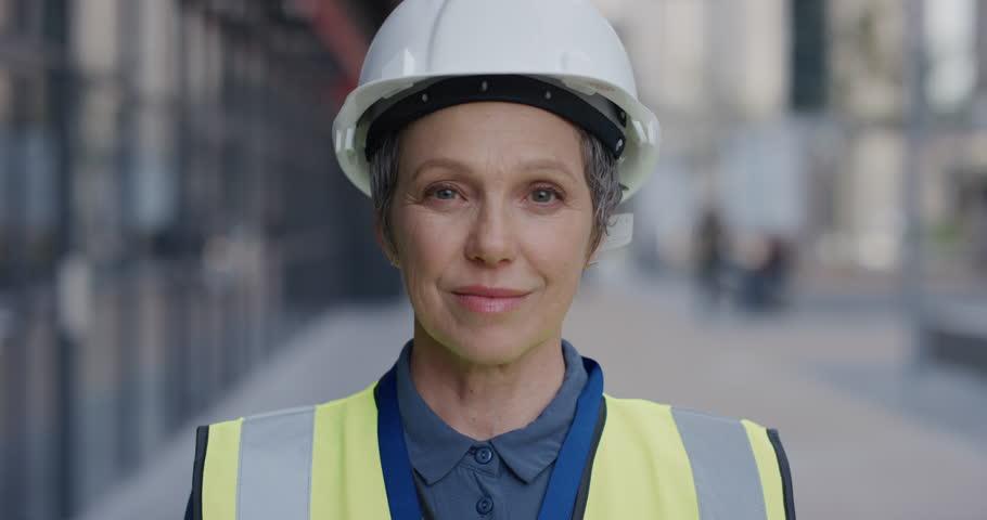 Portrait successful senior construction engineer woman smiling enjoying professional career success wearing hard hat safety helmet slow motion female ambition
