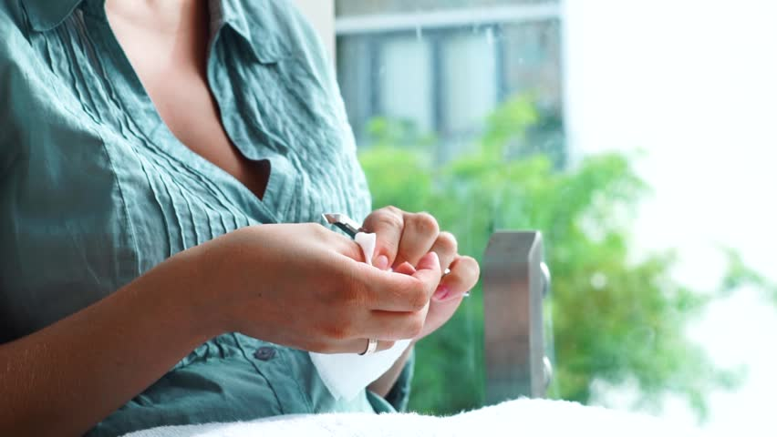 Young woman sitting near window and doing yourself manicure at home. Woman using manicure tools for cut cuticle at home. Home manicure concept