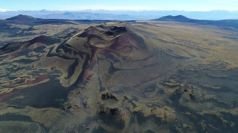 Aerial drone scene of La Payunia National Park in Malargüe, Mendoza. Pampas Negras with black, red ground rocks from volcano and golden grasses pattern. Gravel road. Camera flying over old volcano.