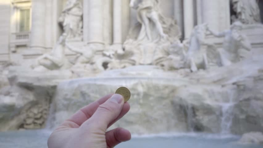 A coin is thrown into the Trevi Fountain. Rome italy