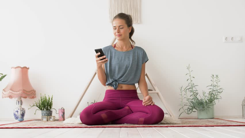 Fitness, technology and healthy lifestyle concept - woman with smartphone meditating at yoga studio | Shutterstock HD Video #1013212658