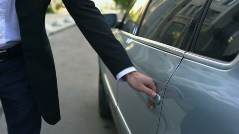Driver opening car door to young respectable oligarch, professional chauffeur