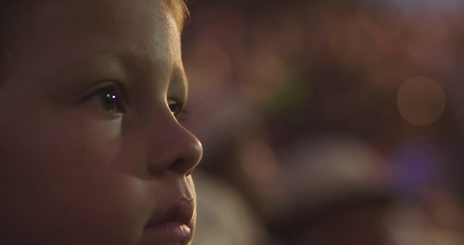 Close-up of a little girl's face watching a show with light effects. Concept of: shows, fireworks, amazement and lights.