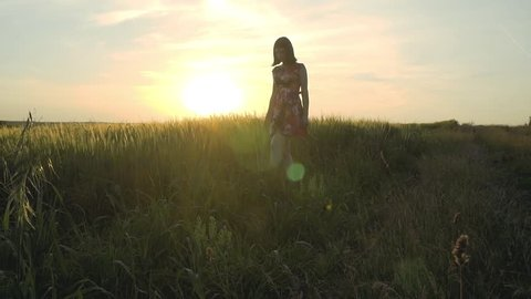 beautiful, attractive European girl with long leggs in short skirt with flowers walks in a rye field against the background of the sunrise , slow motion