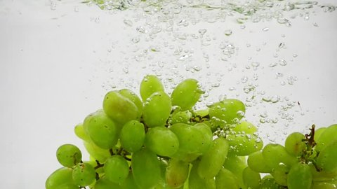 Bunch of green grapes falling into water with bubbles in slow motion. Berries on white background.