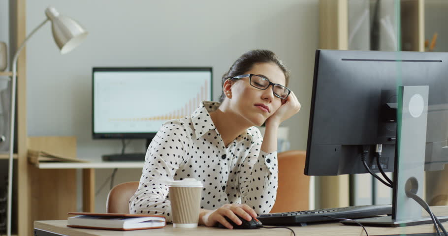 Young tired woman in glasses sitting at the laptop computer while working in the office, then almost falling asleep and waking up. Indoor. #1013276198